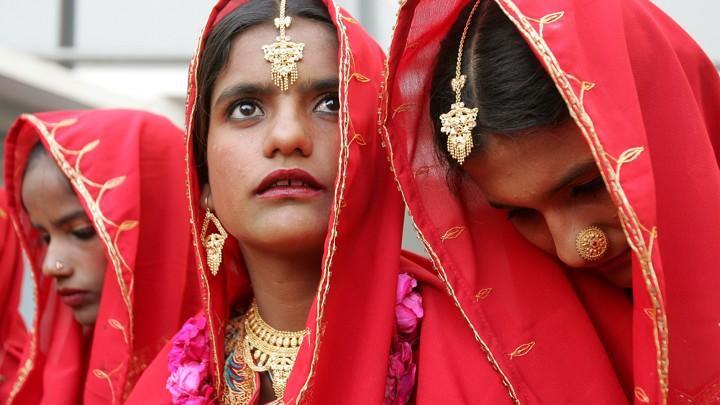 Pakistani brides sit during a mass wedding ceremony in Karachi