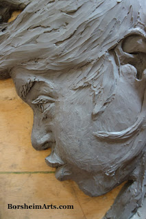 Wind personified as woman in bas relief sculpture