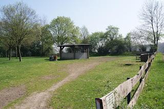 Auf einer Wiese steht eine befestigte Hütte. Rechts davon stehen Bänke.