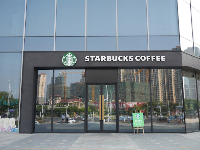 under-construction buildings reflecting off of the front of a Starbucks store in Bengbu