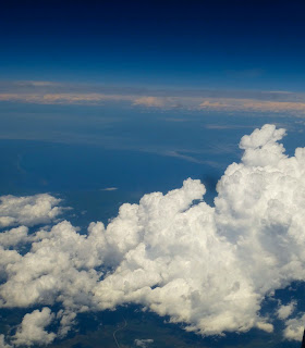 Clouds against the sky and distant earth below