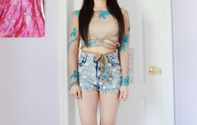 A beach, festival, vacation-ready outfit featuring a For Love and Lemons Orchid crop top dupe floral mesh tie-waist nude top from Romwe, paired with high-waisted embroidered floral acid wash cutoff denim shorts.