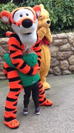 Little boy hugging tigger as pooh bear looks on