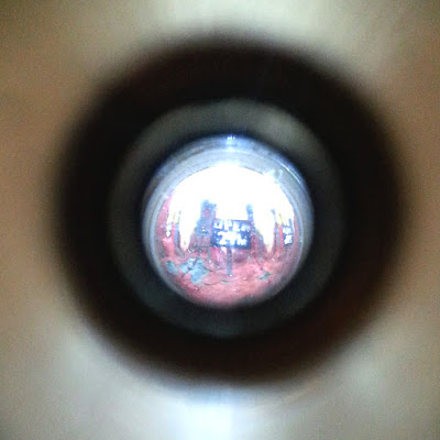 Tiny miniature 'open 24 hrs' sign, seen through a peep hole.
