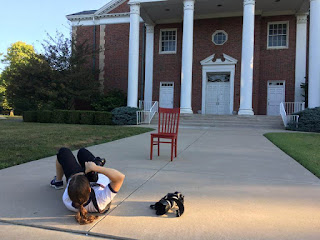 Female photographer lying on the sidewalk photographing a red chair in front of a historic two-story brick church with white columns