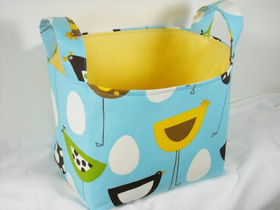 fabric basket with birds and eggs on a blue background; yellow interior