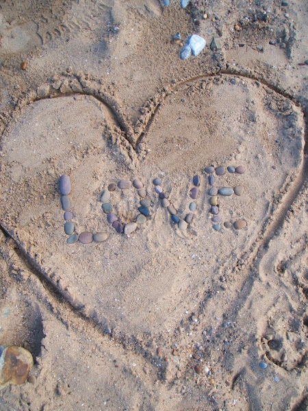 love note written in the sand with pebbles