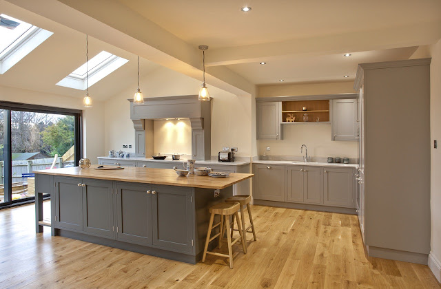 bespoke open plan kitchen diner with bifold doors, Carrara marble and solid oak worktops, farrow and ball Manor House grey and downpipe units, island, integrated appliances, pendant lighting and statement extractor hob. shaker style kitchen inspiration.