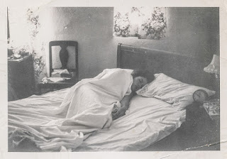 black-and-white photography of a woman sleeping in a bed