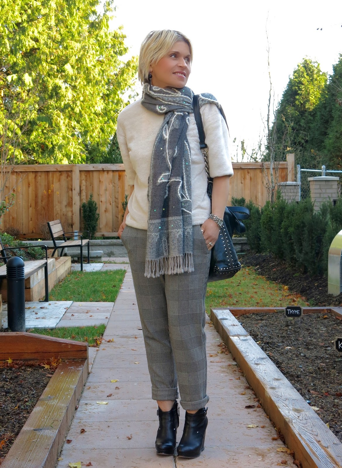 styling a plush tee with slouchy plaid pants, wedge booties, and an embroidered scarf