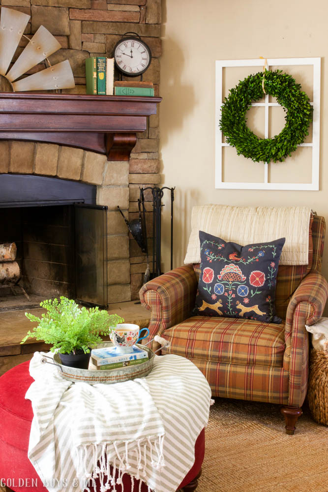 Spring decor with boxwood wreath and Ikea throw pillow by stone fireplace