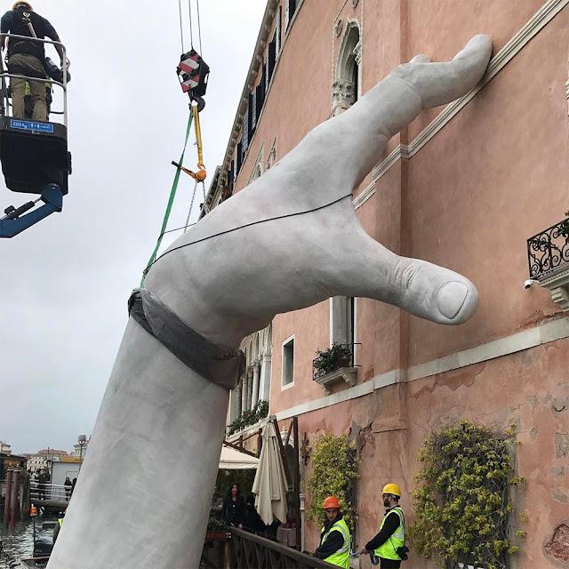 Manos gigantes sostienen un edificio en Venecia para crear conciencia sobre el calentamiento global