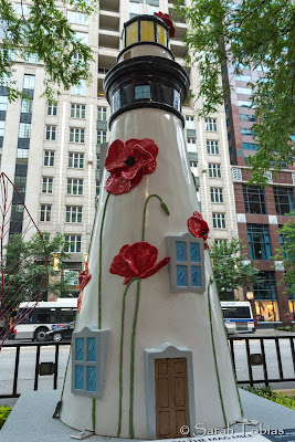 Large three dimensional red poppies on a white lighthouse.