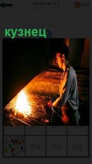 В помещении стоит кузнец около огня и готовит материал для работы