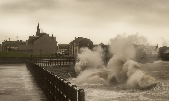 Photo of waves crashing against the sea wall at Maryport promenade