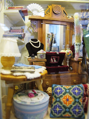 Various items displayed in the window of a one-twelfth scale miniature op shop.
