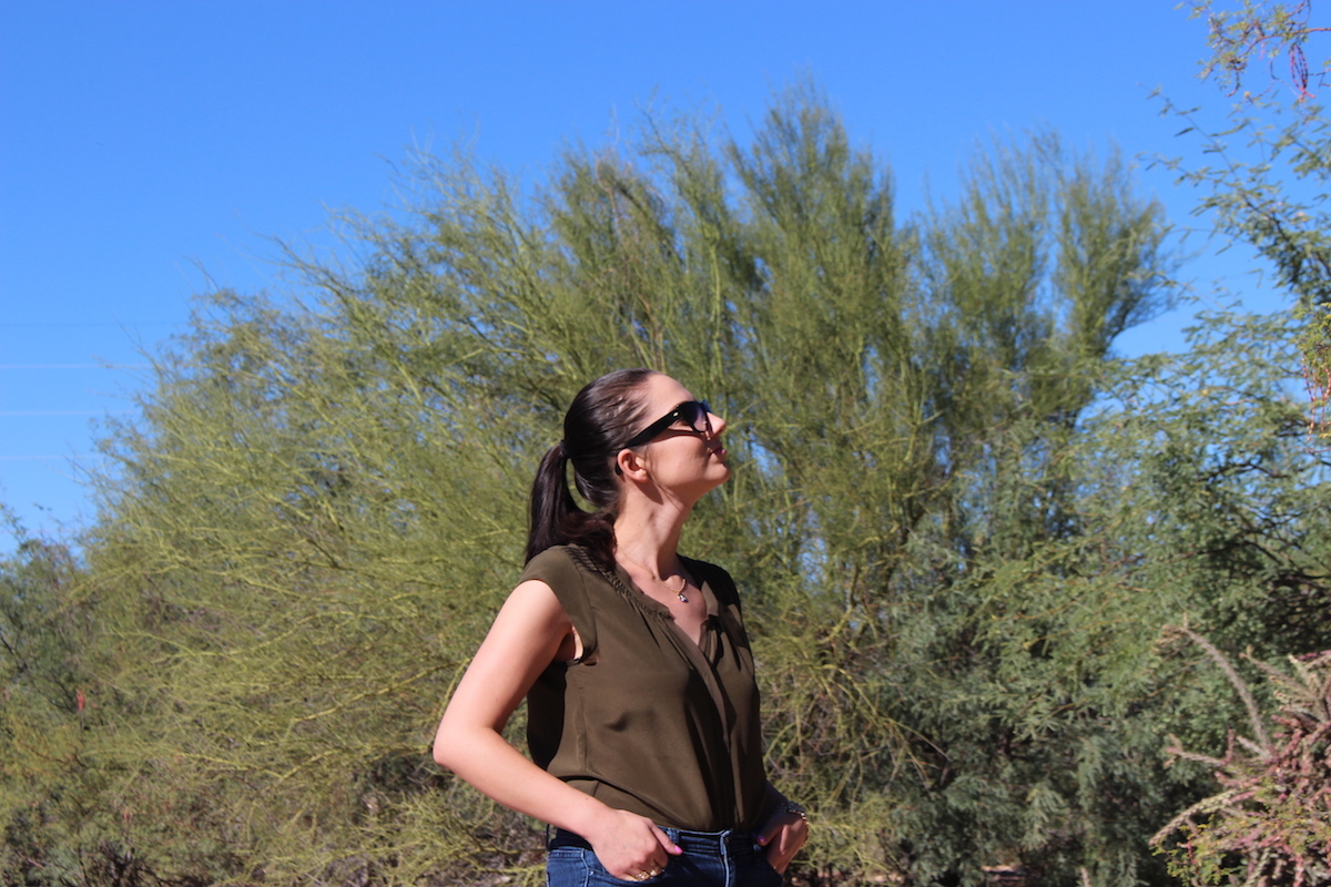In this photo wearing a silk blouse, cat eye sunglasses and jeans, I am standing in the middle of the desert looking up.