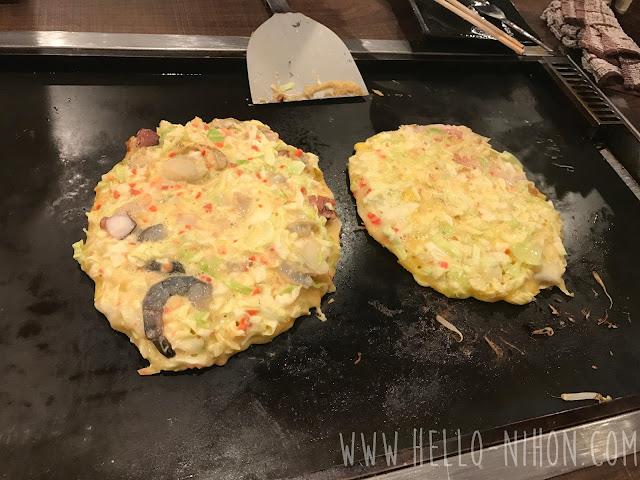 Okonomiyaki cooking on the grill