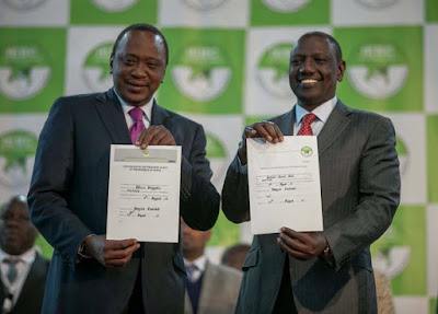 Uhuru Kenyatta with William Ruto being given the Certificate. PHOTO | Courtesy