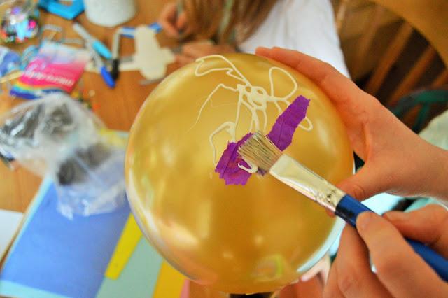 A gold ballon, white glue, tissue paper and paint brush.