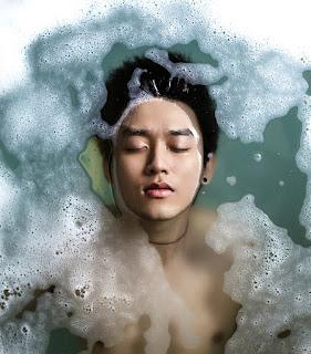 Visão superior de rapaz oriental deitado na banheira de olhos fechados e cabelos mergulhados na água com espuma de shampoo