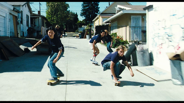 people skateboarding down an alley