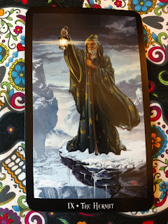 The Hermit -IX card. Old man in brown robes on a cold mountain, holding up a lantern