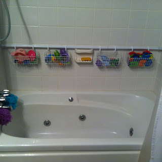 Image: 2nd shower rod against the back wall with wire baskets on curtain hooks to organize bath toys