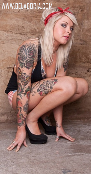 Chica en cuclillas con tatuajes en hombros y tatuaje de ancla en el muslo