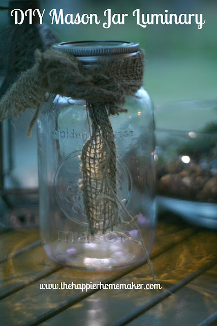 A DIY glass jar with luminary burlap ribbon sitting on a wood table