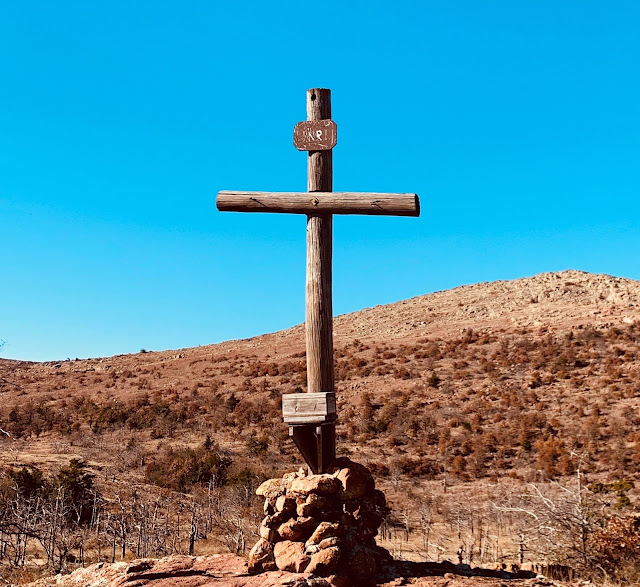 A wooden cross on top of rocks on a mountain