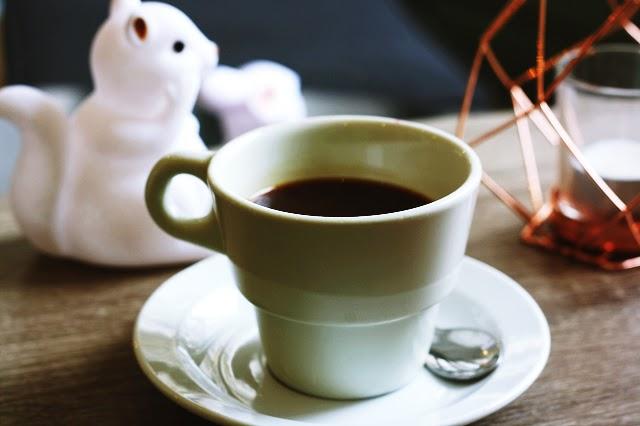 tasse de café pleine sur table en bois et objets de décoration