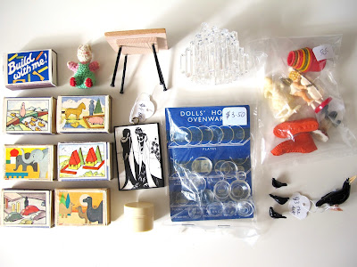 COllection of dolls' house miniature purchases arranged on a desk.