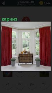 В комнате подвешен карниз и шторы над окнами и стоит диван, две вазы с цветами