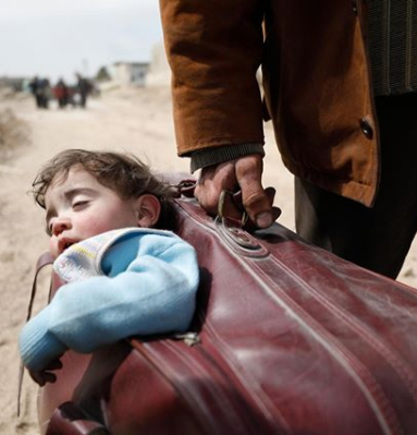 Heartbreaking photo shows a father fleeing war-torn Syria with his son in a suitcase