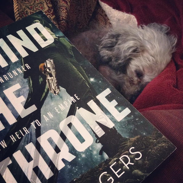 Murchie curls up in a red blanket nest. At an angle in front of him is a trade paperback copy of Behind The Throne. Its cover features the legs and torso of a brown-skinned, green-haired woman clad in green fatigues and a sheer green drape that blows out behind her. She holds a silver gun and stands against a background of stars in a misty grey sky.