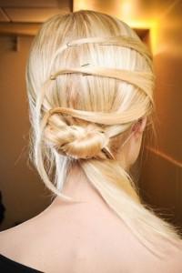 Goldenes, langes, blondes Haar wird einfach dadurch gestylt, dass man den unteren Knoten bindet und dann ein paar Strähnen oben fixiert.