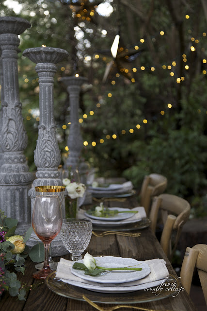 Table setting long view with wine stems and plates and twinkling lights in the background
