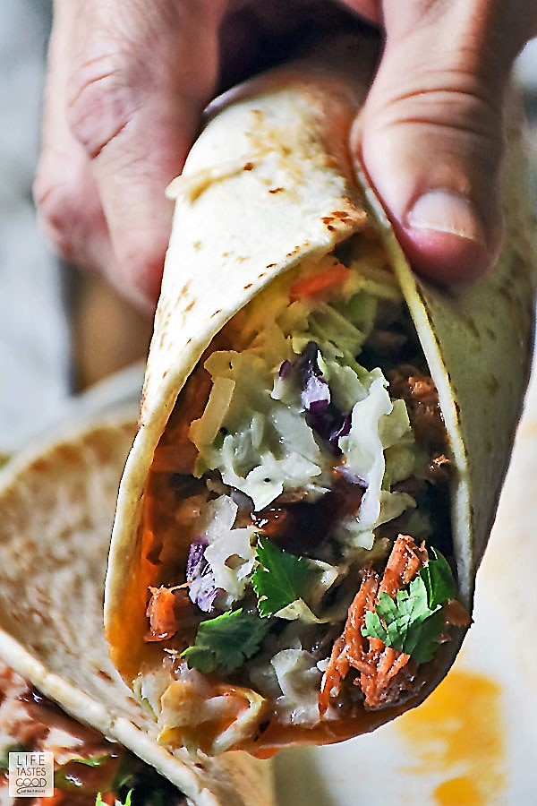 Close up of someone grasping a BBQ Pulled Pork Taco garnished with fresh cilantro ready to take a bite