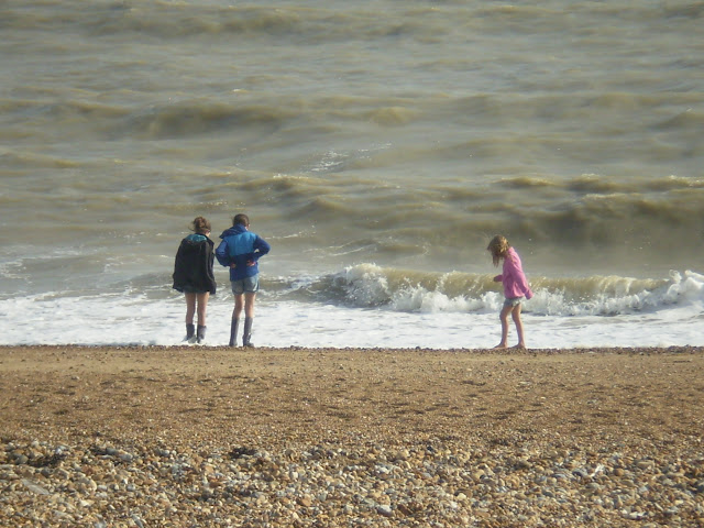 windy beach in summer with children in wellies
