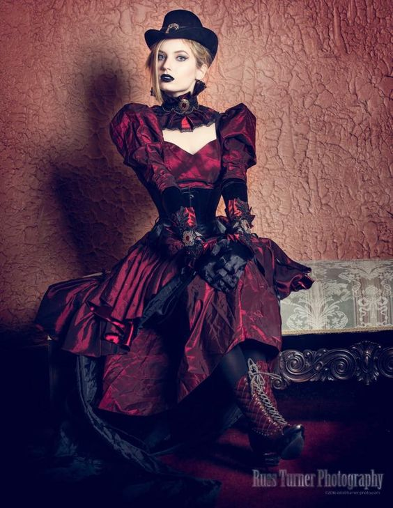 A steampunk woman wearing a victorian burgundy red dress with black underbust corset, hat, and gloves.