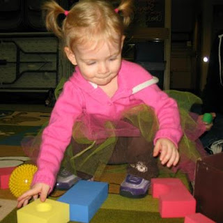 toddler playing with foam blocks, small ball, and scarves