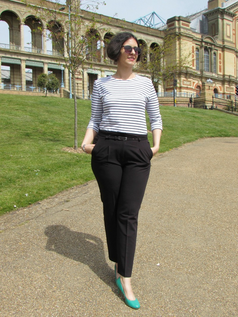 breton top, black trousers and green shoes