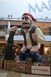 A giant statue of a man defecating. It is in a mall and he is wearing a Santa hat, blue jeans, white shirt and grey vest.
