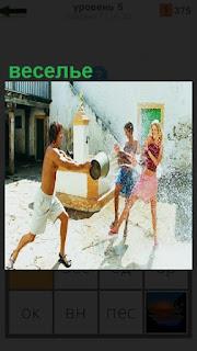 В летнюю жару парень из ведра в качестве веселья обливает водой девушек