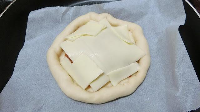 ピザ生地にチーズをたっぷりのせる