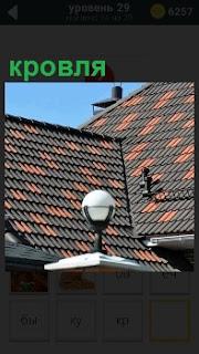 Необычная крыша с красивым орнаментом кровля и на переднем плане стоит фонарь в дневное время