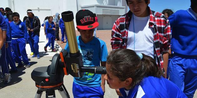 Niña mira por telescopio, mientras otros esperan su turno