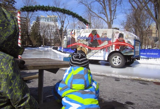 Two small boys watch the Zamboni at the Gage Park skating rink.