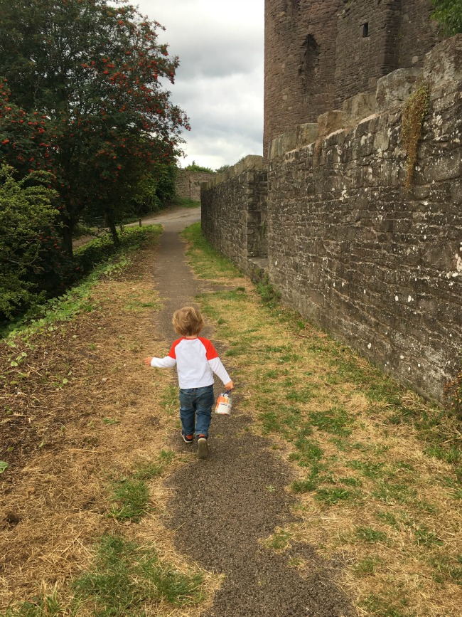Abergavenny-castle-walls-and-a-toddler-carrying-a-bag-full-of-stickers